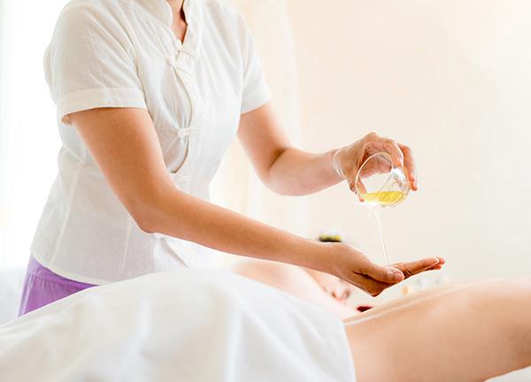 Foto van een vrouw die massageolie aanbrengt - Optimassage: massages op locatie voor bedrijven en particulieren