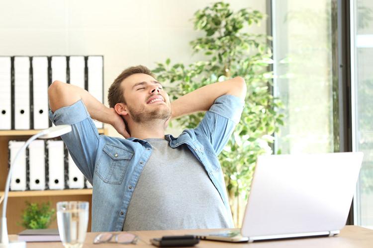 Foto van een ontspannen man achter een bureau - Optimassage: massages op locatie voor bedrijven en particulieren