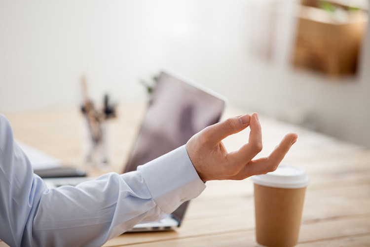Foto van een man met zijn handen in mediatiehouding - Optimassage: massages op locatie voor bedrijven en particulieren